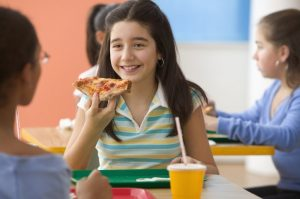 Girl eating pizza at school